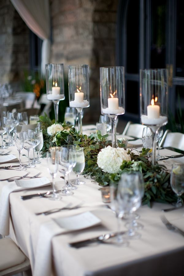 low lush olive leaves white hydrangeas tall stemmed candle holders centerpiece