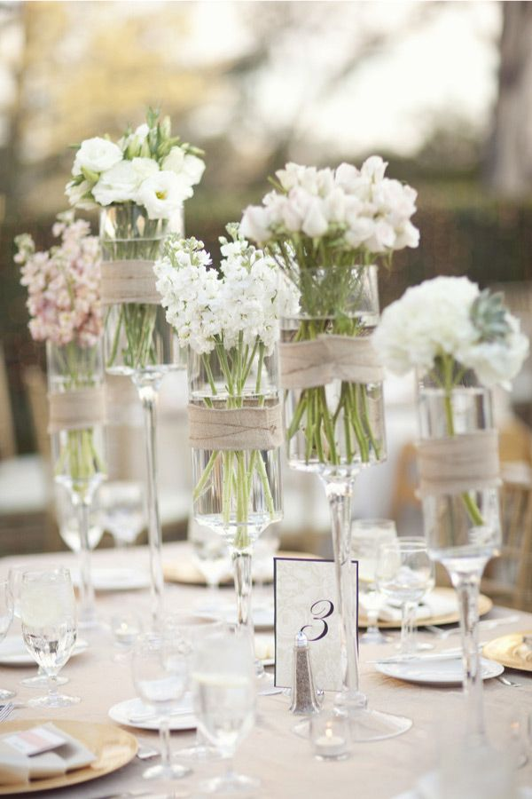 assorted wild white flowers in tall stemmed candle holders wrapped with burlap wedding centerpiece